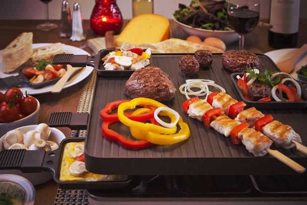Raclette wird in kleinen Pfännchen zubereitet. Verschiedene Zutaten können ganz nach Belieben zusammengemixt werden, dann kommt eine Scheibe Käse darüber und ab in den dafür vorgesehenen Ofen. (#01)