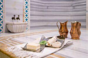 Der Tellak im Türkischen Bad hilft gerne beim Übergießen mit Wasser. Auch seine Peelings und Massagen tragen zum Wohlbefinden bei. (#1)