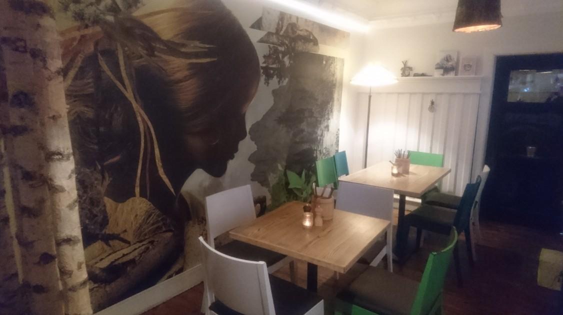 Bergschön Mainz: Der Gastraum erinnert mit vielen Grüntönen und Bergpanorama an Urlaub in den Alpen