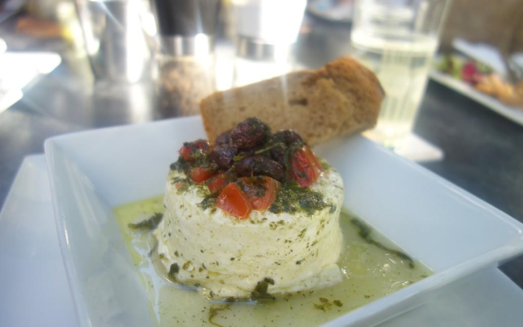 """Gegrillter Kuhmilchfeta aus der Duftfolie mit Kirschtomaten, Oliven, Basilikum-Pesto und Brot. Das Cubo Negro kann auch """"ohne Fleisch""""."""